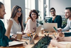 Colleagues become friends. Group of young modern people in smart casual wear discussing something and smiling while working in the creative office stock photography