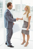 Colleagues with blueprints shaking hands Royalty Free Stock Photo