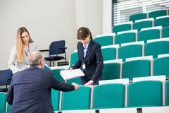 Colleagues With Books In Lecture Hall royalty free stock images