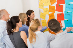 Colleagues Brainstorming In Front Of Whiteboard. Business colleagues brainstorming multicolored labels stuck on whiteboard in meeting Stock Photo