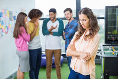 Colleagues bullying a sad female executive. In office Royalty Free Stock Photography