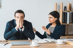 Colleagues in business suits arguing about project details stock images