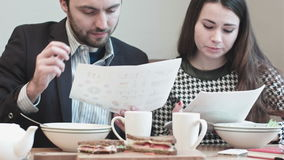 Colleagues at cafe discussing paper documents stock footage