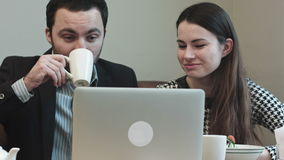 Colleagues at cafe looking on laptop screen and laughing stock footage