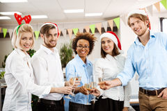 Colleagues celebrating christmas party in office drinking champagne smiling. Royalty Free Stock Images