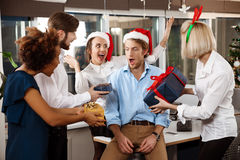Colleagues celebrating christmas party in office smiling giving presents. Happy cheerful colleagues celebrating christmas party in office smiling giving royalty free stock photos