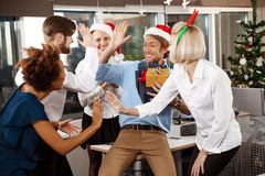 Colleagues celebrating christmas party in office smiling giving presents. Happy cheerful colleagues celebrating christmas party in office smiling giving Stock Photo