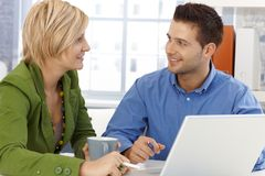 Colleagues chatting. Sitting together at office table, smiling royalty free stock photo