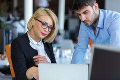 Colleagues chatting, sitting together at office table, smiling royalty free stock photography