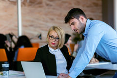 Colleagues chatting, sitting together at office table, smiling royalty free stock image