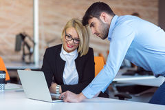 Colleagues chatting, sitting together at office table, smiling royalty free stock photo