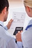Colleagues checking an invoice on a calculator Royalty Free Stock Photography
