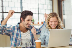 Colleagues cheering in office Stock Photo