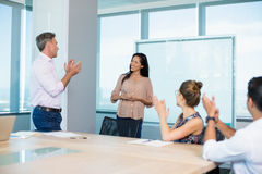 Colleagues clapping for businesswoman in conference room Royalty Free Stock Image