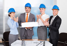 Colleagues Clapping For Man Holding Model Stock Photos