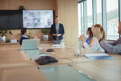 Colleagues clapping during meeting stock image