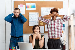 Colleagues closing mouth, eyes and ears with hands in office. See-hear-speak no evil variation. Stock Photos