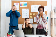 Colleagues closing mouth, eyes and ears with hands in office. See-hear-speak no evil variation. Colleagues closing mouth, eyes and ears with hands in office royalty free stock images
