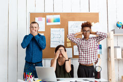 Colleagues closing mouth, eyes and ears with hands in office. See-hear-speak no evil variation. Colleagues closing mouth, eyes and ears with hands in office royalty free stock photography
