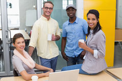 Colleagues with coffee cups during break at office Royalty Free Stock Images