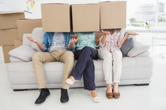 Colleagues covering with cardboard box gesturing Stock Image