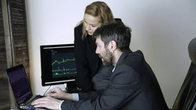 Colleagues discuss currency changing on a stock exchange. watching currency exchange chart at laptop.  stock video