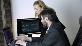 Colleagues discuss currency changing on a stock exchange. watching currency exchange chart at laptop.  stock video footage