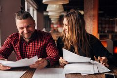Colleagues discuss documents sitting in a cafe Royalty Free Stock Photos