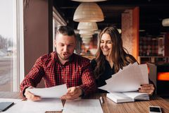 Colleagues discuss documents sitting in a cafe Stock Images