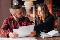 Colleagues discuss documents sitting in a cafe stock image