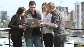Colleagues discuss work in an informal setting on the roof of an office building. Businessmen work in the outdoor. The stock video