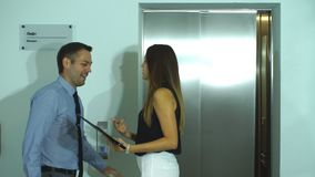 Colleagues discuss a work plan near the Elevator. Businesswoman showing colleague business idea stock footage