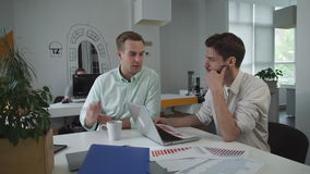 Colleagues discussing financial report in the modern office. Young business men sitting at the working place and drinking coffee. On the table cup computer stock footage