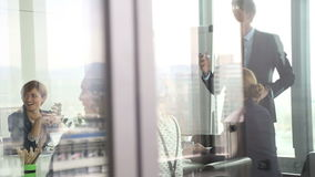 Colleagues discussing on a meeting in conference room, behind glass wall stock video footage