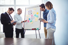 Colleagues discussing in meeting room using white board. At creative office Royalty Free Stock Images
