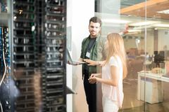 Colleagues discussing in office server room. Two business people standing in server room with laptop and discussing royalty free stock image