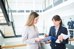 Colleagues Discussing Over Documents By Railing In Office royalty free stock photo