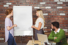 Colleagues discussing over whiteboard in office Royalty Free Stock Photography