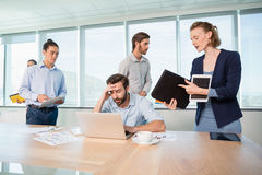 Colleagues with document, digital tablet and mobile phone talking to frustrated man. In office Stock Image