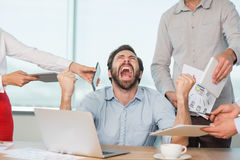 Colleagues with document, digital tablet and mobile phone talking to frustrated man. In office Royalty Free Stock Photos