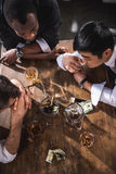 Colleagues drinking alcohol while spending time together Stock Photography