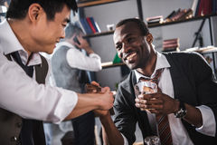 Colleagues drinking alcohol while spending time together after work Royalty Free Stock Photos
