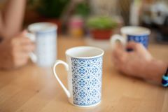 Colleagues drinking coffee at home office. Seated at a table with focus to a third blue and white patterned mug in the foreground center and their hands visible stock photo
