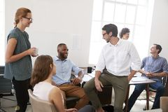 Colleagues enjoying a casual meeting in their office, close up royalty free stock photo
