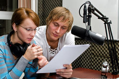 Colleagues examine broadcast list Stock Images