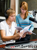 Colleagues examine broadcast list Royalty Free Stock Images