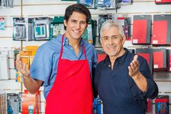 Colleagues Gesturing Together In Hardware Store Royalty Free Stock Photography
