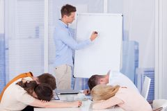 Colleagues getting bored during business presentation Stock Photo