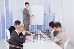 Colleagues getting bored during business presentation. Given by businessman in office royalty free stock photos