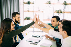 Colleagues giving high-five in meeting room at creative office royalty free stock photo